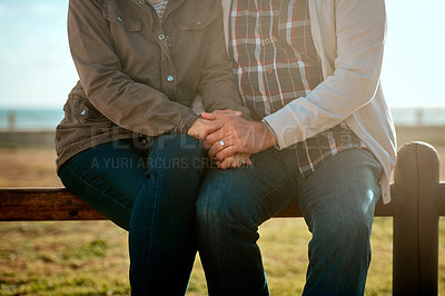 Buy stock photo Cropped shot of an unrecognizable senior couple sitting on a wooden railing at the beach