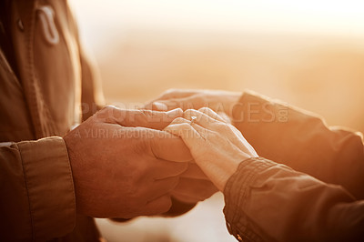 Buy stock photo Cropped shot of an unrecognizable senior couple standing hand in hand at the beach