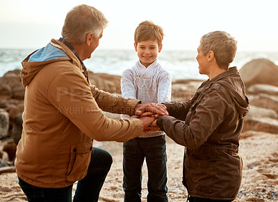 Buy stock photo Cropped shot of an adorable little boy and his grandparents standing with their hands in a huddle at the beach