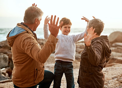 Buy stock photo Cropped shot of an adorable little boy and his grandparents high-fiving at the beach