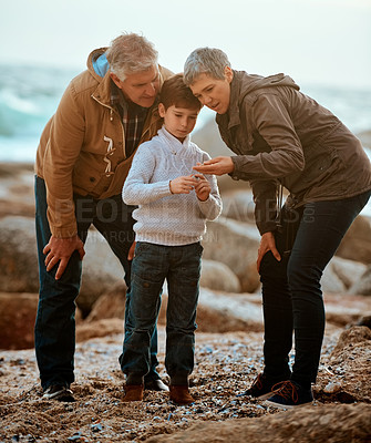 Buy stock photo Full length shot of a senior woman showing her grandson something while at the beach