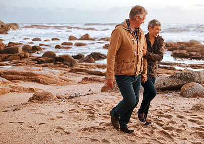 Buy stock photo Full length shot of an affectionate senior couple walking hand in hand on the beach