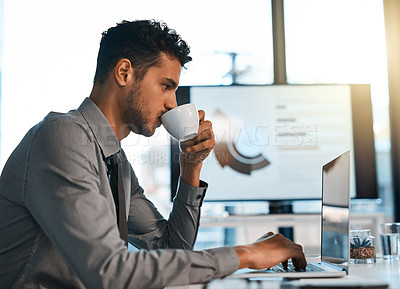 Buy stock photo Shot of a young businessman drinking coffee while working on a laptop in an office