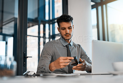 Buy stock photo Shot of a young businessman using a cellphone and laptop in an office