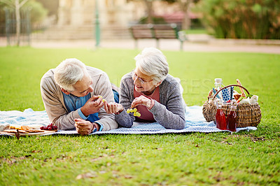 Buy stock photo Shot of a loving senior couple enjoying a leisurely picnic at the park