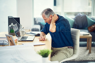 Buy stock photo Cropped shot of a senior man experiencing body pain while working from home