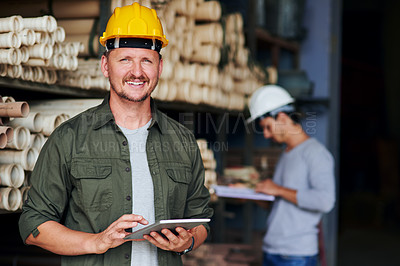 Buy stock photo Cropped portrait of a handsome mature construction worker using his tablet while standing in an industrial warehouse
