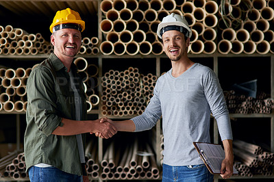 Buy stock photo Cropped portrait of two male construction workers shaking hands while standing in an industrial warehouse