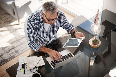 Buy stock photo High angle shot of a mature man working on a digital tablet and laptop at home