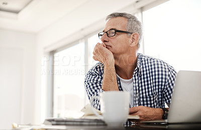 Buy stock photo Shot of a mature man looking thoughtful while working on a laptop at home