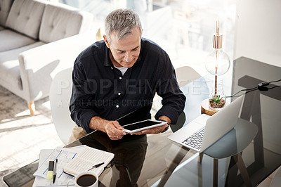 Buy stock photo High angle shot of a mature man working on a digital tablet at home