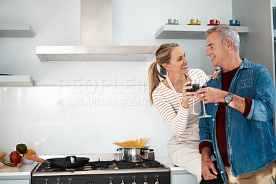 Buy stock photo Cropped shot of a mature couple enjoying a glass of wine at home