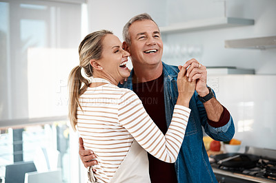 Buy stock photo Cropped shot of a couple dancing in their kitchen