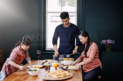 Buy stock photo Shot of a young family having a meal together at home