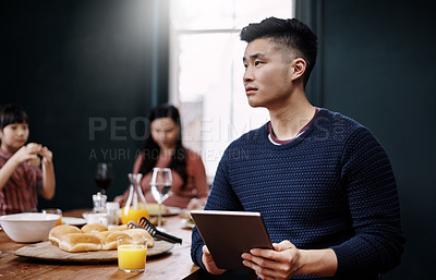 Buy stock photo Shot of a young family having a meal together while the father uses a tablet at home