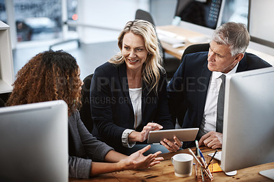 Buy stock photo Shot of a group of businesspeople working on a computer and digital tablet together in an office
