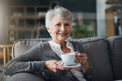 Buy stock photo Portrait of a senior woman enjoying a beverage while relaxing on the sofa at home