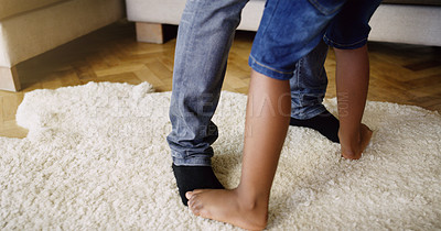 Buy stock photo Cropped shot of an unrecognizable father and son dancing together at home