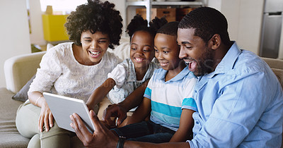 Buy stock photo Cropped shot of a young family using a tablet together while chilling on the sofa together in the living room at home