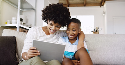 Buy stock photo Cropped shot of a young beautiful mother using a tablet with her adorable little son while chilling on the sofa at home