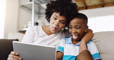 Buy stock photo Cropped shot of a young beautiful mother and her adorable little son taking a selfie using a tablet while chilling on the sofa at home