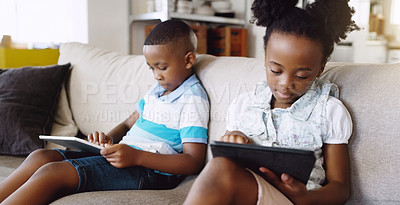 Buy stock photo Cropped shot of an adorable little brother and sister using tablets while chilling on the sofa at home