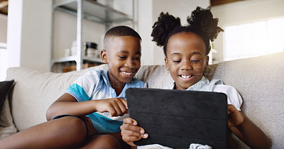 Buy stock photo Cropped shot of an adorable little brother and sister using a tablet together while chilling on the sofa at home