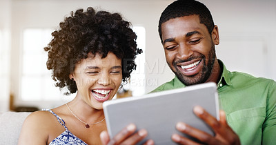 Buy stock photo Cropped shot of a married couple watching a move together on a tablet while chilling on the sofa at home