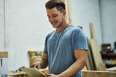 Buy stock photo Cropped shot of a carpenter using a digital tablet in his workshop