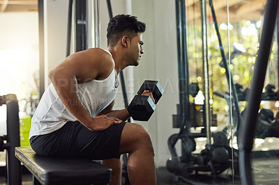 Buy stock photo Shot of a young man working out with weights in a gym