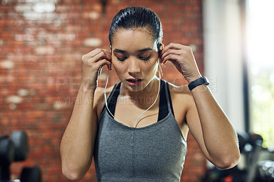 Buy stock photo Shot of a young woman putting on earphones in a gym