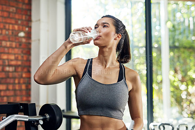 Buy stock photo Shot of a young woman drinking water in a gym
