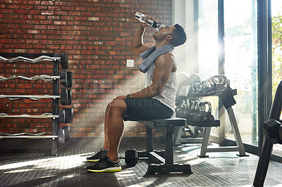 Buy stock photo Shot of a young man drinking water in a gym