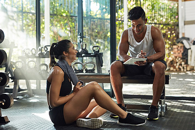 Buy stock photo Shot of a young couple using a digital tablet together in a gym