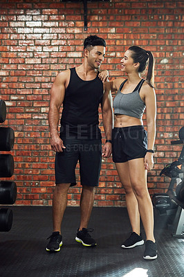 Buy stock photo Shot of a young couple working out together in a gym