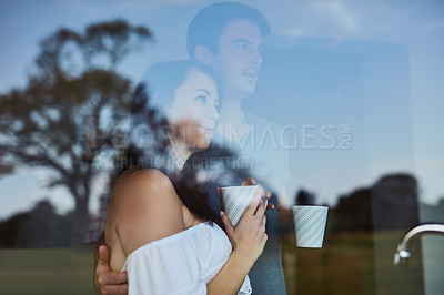 Buy stock photo Shot of a young couple drinking coffee while looking out the window at home