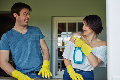 Buy stock photo Shot of a young couple having fun while cleaning together at home