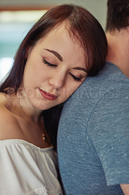Buy stock photo Shot of a young woman resting on her boyfriend's shoulder at home
