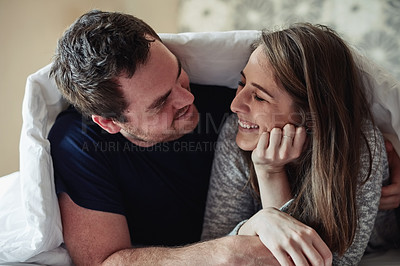 Buy stock photo Shot of a happy young couple covering themselves with a blanket on the bed at home