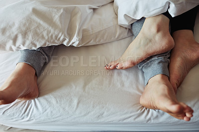 Buy stock photo Shot of an affectionate couple's feet poking out from under the bed sheets