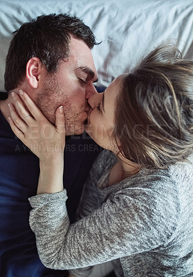 Buy stock photo High angle shot of a happy young couple kissing in bed at home