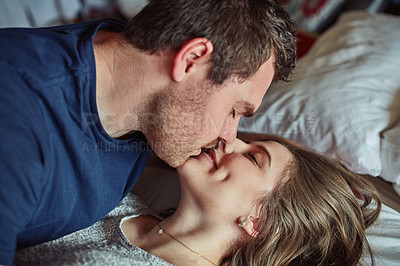 Buy stock photo Shot of a happy young couple kissing in bed at home