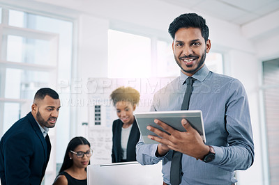 Buy stock photo Shot of a businessman using a digital tablet in an office with his colleagues in the background