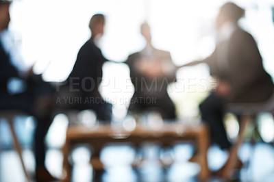 Buy stock photo Blurred shot of two unrecognizable businesspeople shaking hands during a meeting in the boardroom