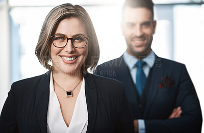 Buy stock photo Cropped portrait of an attractive young businesswoman standing in the office with a male colleague at her back