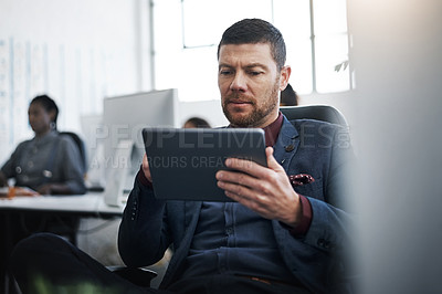Buy stock photo Shot of a mature businessman using a digital tablet at his desk in a modern office