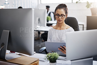 Buy stock photo Shot of a young businesswoman using a digital tablet at her desk in a modern office