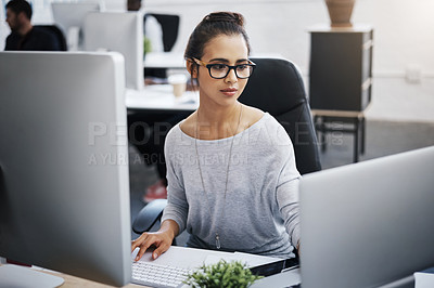 Buy stock photo Shot of a young businesswoman using a laptop and computer at her desk in a modern office