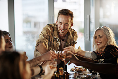 Buy stock photo Shot of a group of young friends making a toast at a dinner party