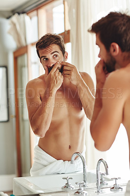 Buy stock photo Cropped shot of a shirtless young man popping pimples in the bathroom mirror